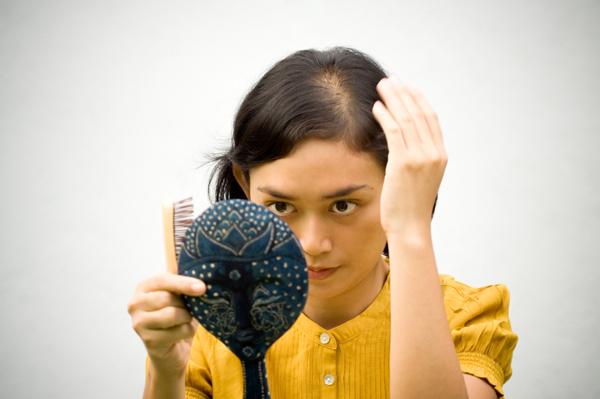 женщина видит в зеркале поредение волос